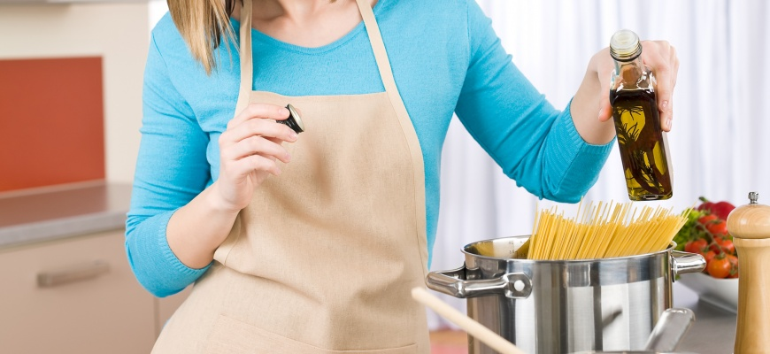 Young Woman Cooking On Gas Range